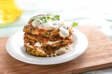 Plate with zucchini pancakes and sauce on wooden board