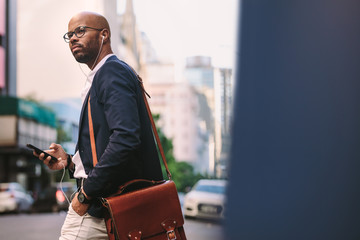 African businessman with bag walking on the street