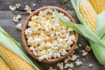 Prepared popcorn in wooden bowl, corncobs on table. Top view.