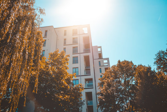big apartment complex with white facade in warm sunlight and framed by orange colored autumn trees