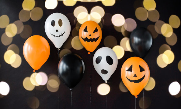 holidays, decoration and party concept - air balloons with funny and evil faces for halloween over lights on black background