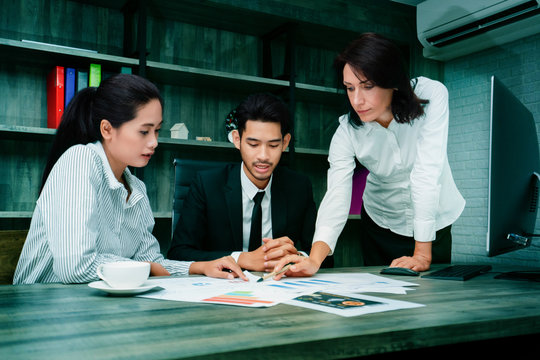 Businessmen are brainstorming about marketing plans, with team providing information from research. Data is stored at the computer. The good work strategy, the work will be successful as it is laid.
