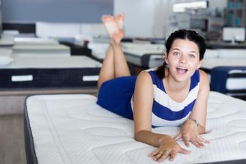 Happy woman lying on comfortable mattress