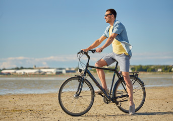people, leisure and lifestyle concept - happy young man riding bicycle along summer beach
