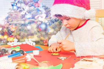 Boy in Santa costume decorating holiday ornaments