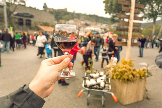 Wine in glass and tourist tasting it at annual city festival Tbilisoba with crowd of people around. Tbilisi, the capital of Georgia country.
