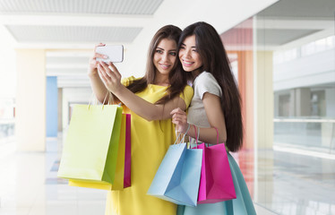 Happy girls taking selfie while shopping in mall