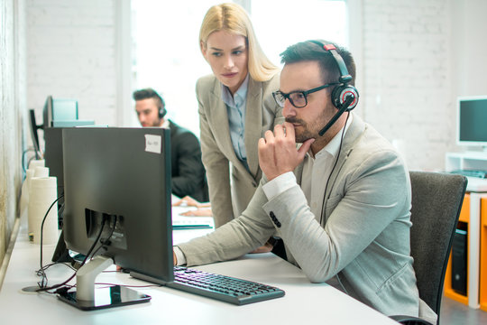 Businesswoman trying to solve online problem with her male colleague at office