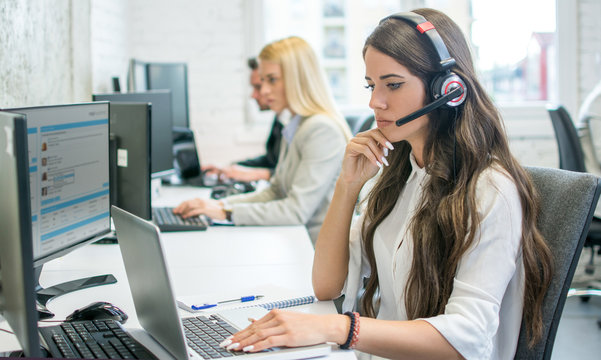 Pensive businesswoman talking on headset while working on laptop in office
