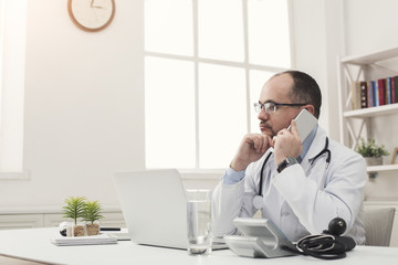 Serious doctor talking on phone with his patient