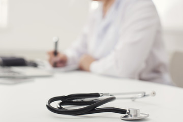 Stethoscope on desk, doctor taking notes