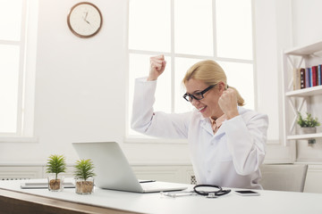 Excited doctor in glasses sitting at desktop