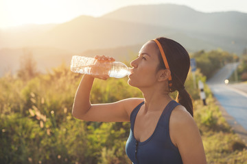 sport woman drinking water during morning jogging