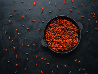 Goji berries in a pan on a black wooden table.