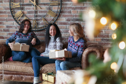 Young women surprise each other with Christmas gifts\