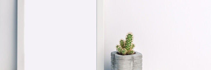 Panoramic photo of a white mockup frame with a cactus in a concrete pot on an empty white background