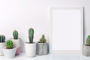 White mockup frame with cactuses in concrete pots on an empty white background