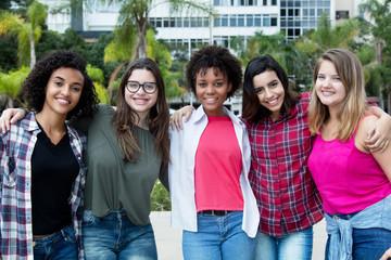 5 junge sympathische Frauen Arm in Arm