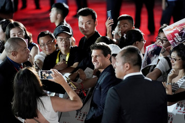 """Cast member Tom Cruise poses for a photo with fans after a news conference promoting his upcoming film """"Mission: Impossible - Fallout"""" in Beijing"""