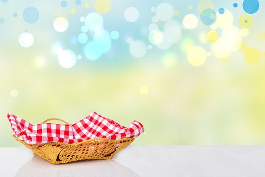 Empty basket with red checkered napkin on white table  in front of beautiful abstract bright sunny background. Template for your product display montage. Beautiful texture. Space on right site.