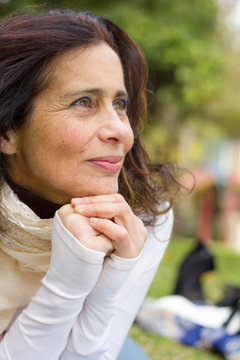 Lovely middle aged woman with hands together below chin and confident look in her eyes. Visionary mature lady with hopeful, positive expression. Pensive, planning, freedom, retirement, single concepts