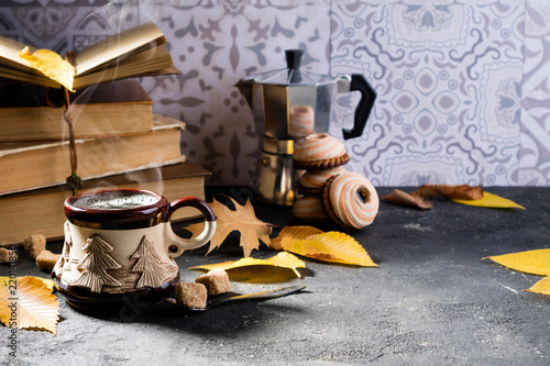 b97e4f4fc18 Autumn composition with coffee. Steaming coffee cup, autumn leaves, books,  cookies and coffee pot. Autumn background with cozy home atmosphere
