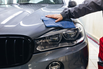 Car detailing: the man holds the microfiber in hand.