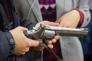 Man is holding a revolver in a gun shop. Sales