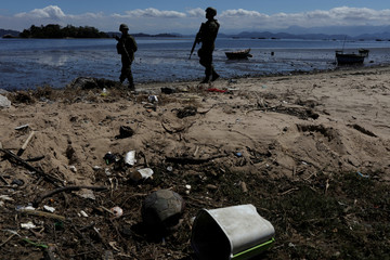 Brazilian soldiers patrol on the banks of the Guanabara Bay during an operation against drug gangs in Salgueiro slums complex in Sao Goncalo, near Rio de Janeiro
