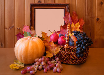 Fresh fruits in basket, pumpkin and picture frame on wooden table