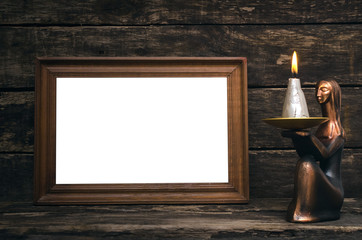 Empty photo frame and burning candle on aged wooden table background.
