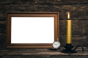Empty photo frame, pocket watch and burning candle on aged wooden table background.