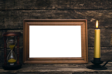 Empty photo frame, sand watch and burning candle on aged wooden table background.