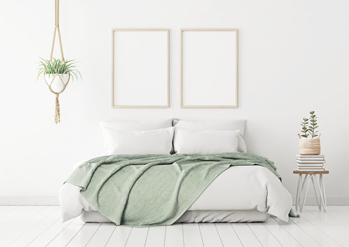 Poster mockup with two vertical frames on empty white wall in bedroom interior with bed, green plaid and plants. 3D rendering.