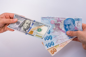 Hands holding American dollar banknotes and Turksh Lira banknotes side by side