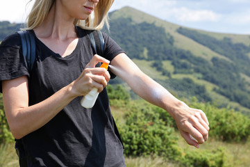 Woman hiker applying Sunscreen spray / sunblock lotion outdoors during summer hike holidays