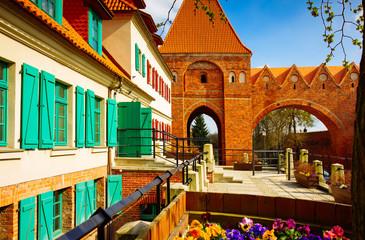 Obraz Toruń, ulica na starym mieście z wieżą zamku krzyżackiego - fototapety do salonu