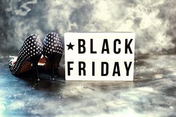 Black friday sale word on lightbox on dark table top view