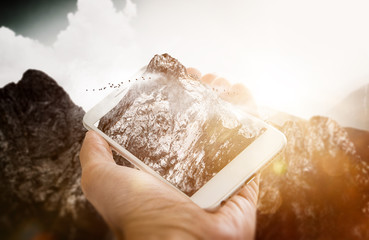 Hand holding white smartphone in front of mountain