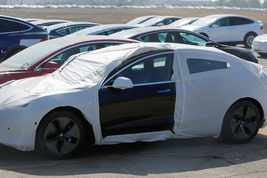 Newly manufactured Tesla vehicles as shown parked in a large lot next to the airport in Burbank, California