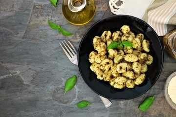 Gnocchi with pesto sauce. Top view scene over a dark stone background with copy space.