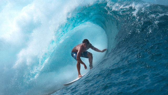 CLOSE UP: Crystal clear water splashes over surfer riding an epic barrel wave.