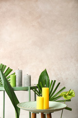 Creative composition with candles and tropical plants on color background