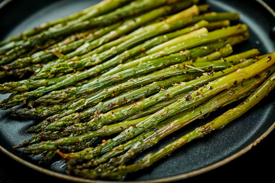 delicious and juicy green asparagus in a pan on an old wooden black table