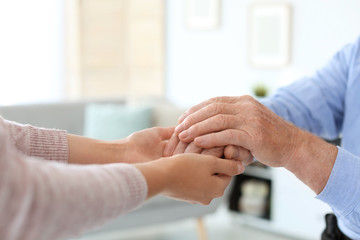 Helping hands on blurred background, closeup. Elderly care concept Fotomurales