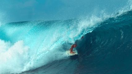 CLOSE UP: Unrecognizable male tourist surfing a cool turquoise barrel wave.