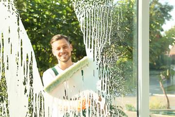 Obraz Male janitor cleaning window, view from inside - fototapety do salonu