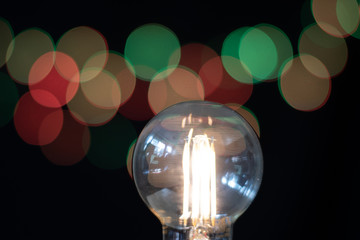 Bare Lightbulb In Foreground And Black Background With Small Lights Showing Bokeh.