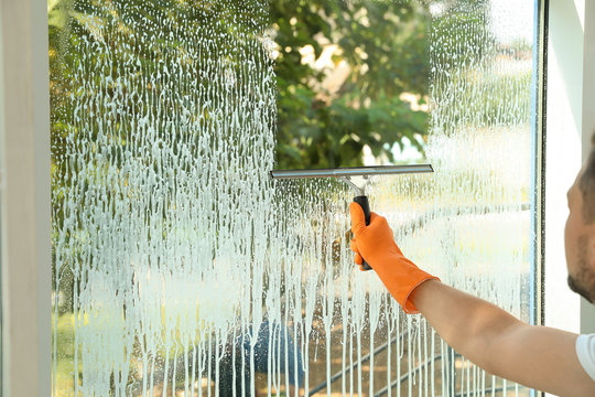 Male janitor cleaning window with squeegee, closeup