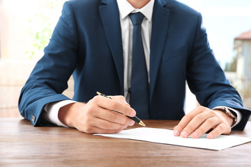 Lawyer working with documents at table, focus on hands